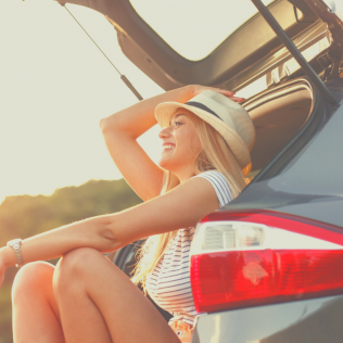 Woman sits in back of rentla hatchback of Shore Rentals