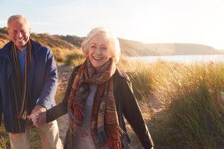happy elderly couple walking on beach