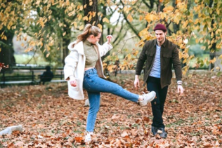 happy couple in park surrounded by fallen leaves