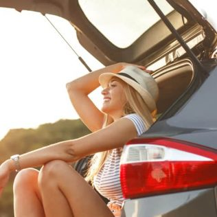 smiling woman sitting in back of car