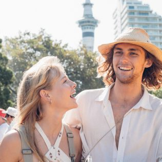 A-couple-laughing-in-a-city-park-with-people-the-Auckland-Sky-Tower-and-a-high-rise-building-behind-them