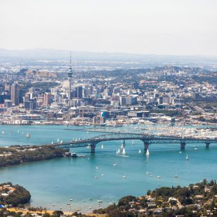 Aerial view of Auckland city featuring ocean and harbour bridge