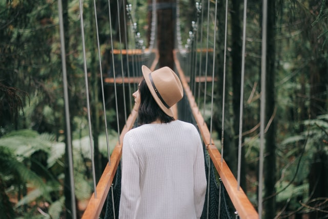 girl walking along a bridge surrounded in forest.