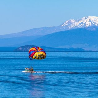 boat in lake taupo with mountain in background